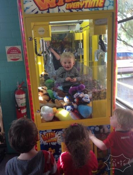 孩子被困在技能测试机。他在等待伙计们投硬币把他救出