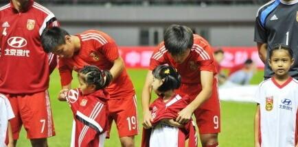 中国之队国际足球友谊赛:中国VS约旦。当地晚上气温下降,赛前,杨旭和武磊脱衣为小球童们御寒。暖暖的,有没有?