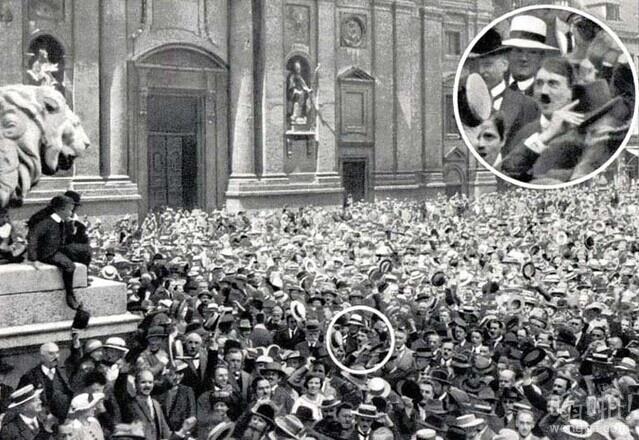 1914年 – 青年阿道夫·希特勒在人群当众庆祝第一次世界大战的集会