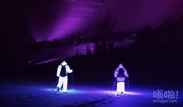 在黑暗中发光的做法!滑雪者他们在山上穿LED夜光服滑雪为了拍摄一个壮观的视频