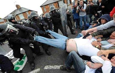 警方和示威者帮助一个胖子扒裤子