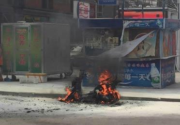 男子摩托车被交警查扣 泼汽油烧车 现场图