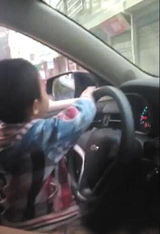 【视频】四五岁小男孩开车穿行闹市 车技娴熟