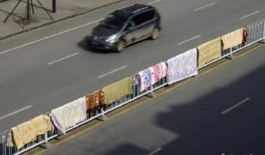 """市民晒被子""""占领""""马路 用道路隔离栅栏晒被子  网友:太危险!"""