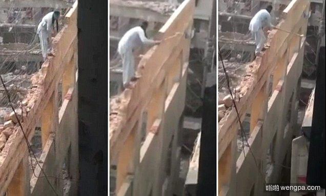 站在墙上拆墙 视频实拍建筑工人站危墙上拆墙