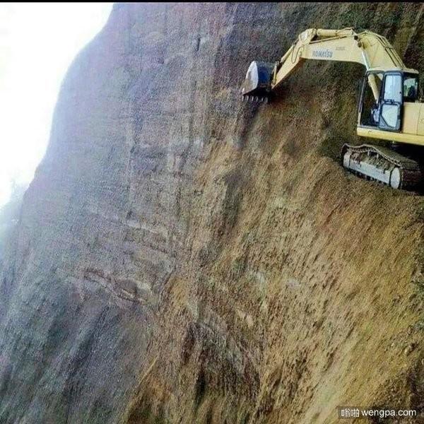 挖掘机在悬崖上凿出一条天路
