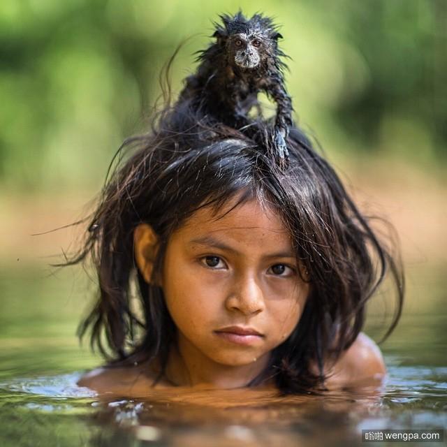 Yoina,一个9岁的女孩来自秘鲁亚马逊Machiguenga社区,与她的宠物鞍背狨