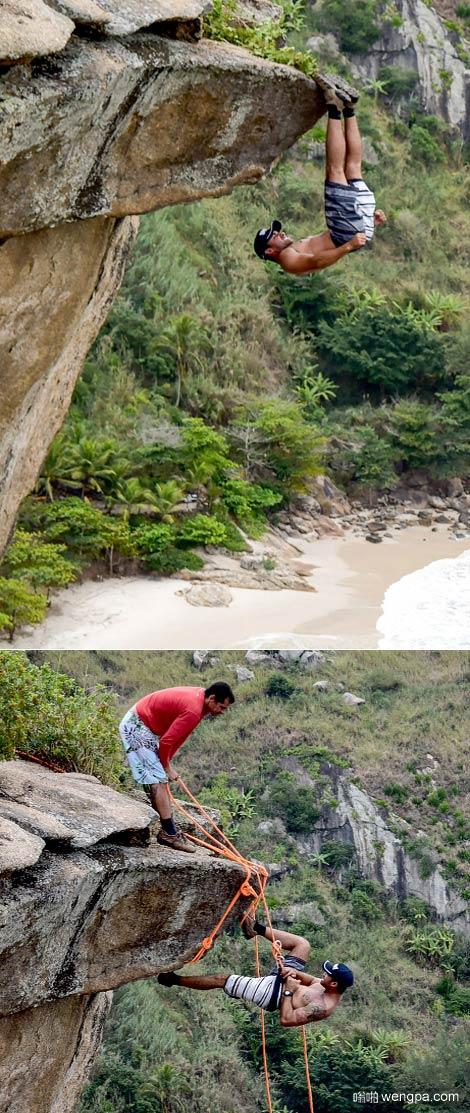 极限运动爱好者没有任何保护装置倒挂在里约热内卢海边悬崖