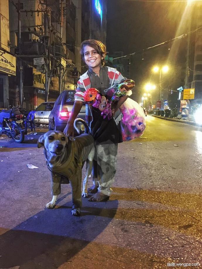 巴基斯坦一位制片人拍到的一幕。夜晚的街道,一个衣衫褴褛还没有鞋的小男孩,把最宝贵的长袖毛衣穿在小狗伙伴身上。笑得很温暖,仿佛拥有了全世界