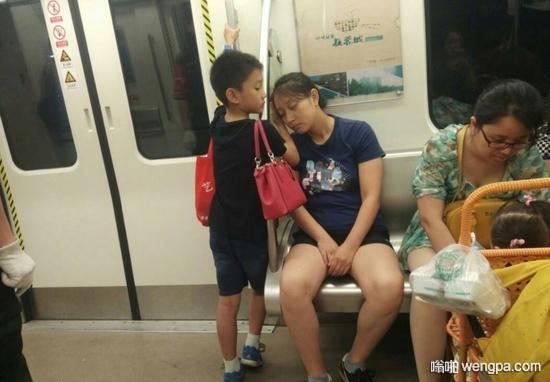 小朋友把位置让给旁边的阿姨,然后背着妈妈的包包,让妈妈靠着自己的手睡觉