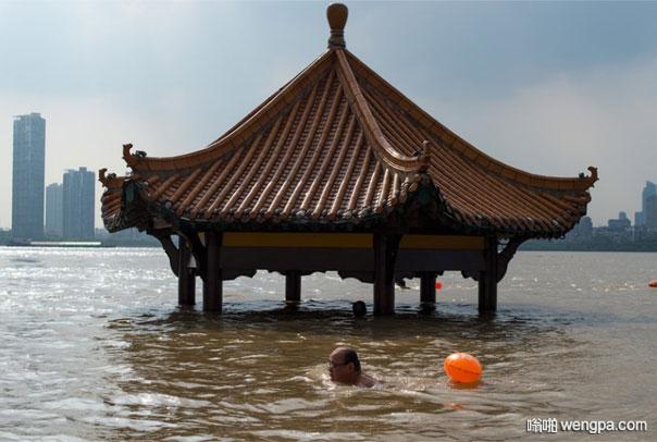 武汉三镇江滩公园被淹 大叔淡定游泳避暑